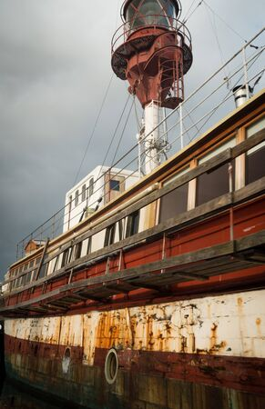 Old and partial rusty red and white houseboat on Copenhagen canal with cloudy grey sky. No people visible.