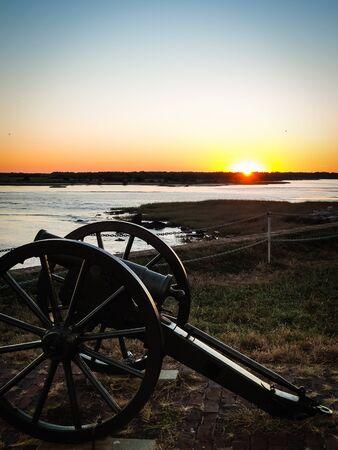 Historic civil war cannon on Fort Sumter island near Charleston, South Carolina before beautiful orange sunset. No people visible, copyspace.