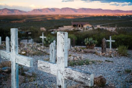 Two wooden cross grave markers overlooking hills in famous Boothill graveyard in Tombstone, Arizona. Sunset in distance, no people visible.