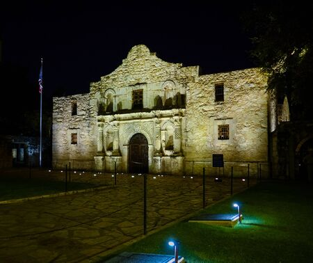Nighttime frontal shot of famous Alamo mission in San Antonio, Texas. Illuminated facade of historic building. Dark night, no people visible.