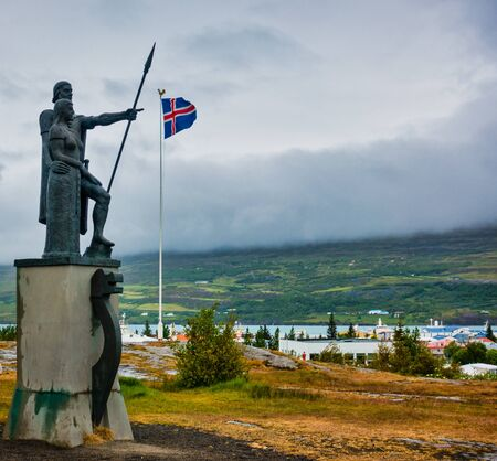 Landnemar status in Akureyri Iceland pointing to icelandic flag on cloudy day. Mountains and fog in background, Great abstract. No people visible.