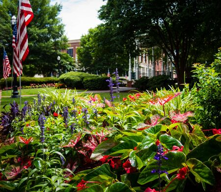Flower bed and pavillon at Marietta Square in Georgia decorated for Independence Day. American Flag waving over lush green plants. Small town square, patriotic scenery. No people visible.