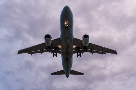 underneath: airplane taking off seen from underneath against a cloudy overcast sky Stock Photo