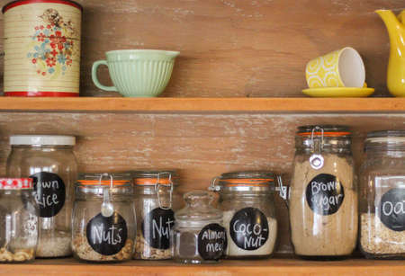 Wooden Antique Kitchen Hutch with jars of baking ingredients and retro crockery Foto de archivo