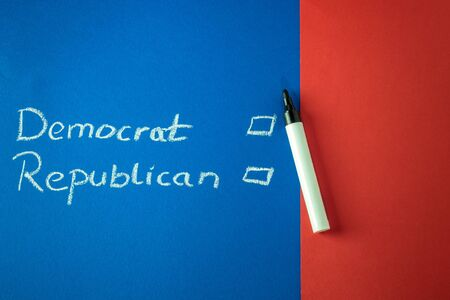 checkboxes: Democrat and Republican and checkboxes written with chalk on red and blue background. Copy space