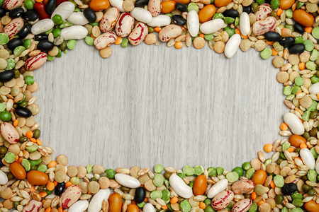 Mixed dried legumes and cereals arranged around grey wooden background. Copy space in middle