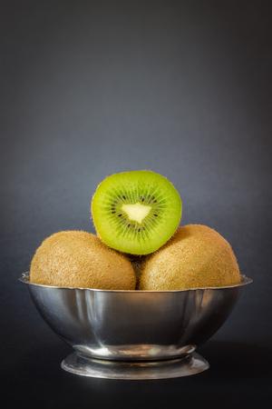 kiwi fruta: El kiwi en un recipiente met�lico sobre fondo oscuro