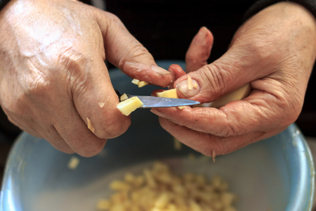 he old: Closeup of old mans hands while he is slicing potatoes Stock Photo