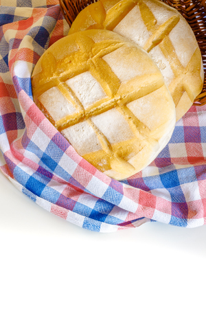 weaved: Two round loafs of bread wrapped in kitchen rag and weaved basket on white background. Copy space