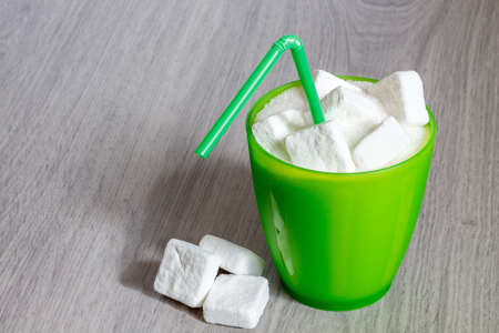 Green plastic glass with straw full of sugar and sugar cubes. Concept image for too much sugar in sodas, juices, beverages, soft and fizzy drinks. Copy space