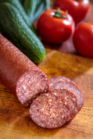 dry sausage: Sujuk sausage on wooden cutting board with fresh vegetables in background. Copy space Stock Photo