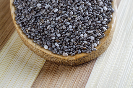 super macro: Closeup of chia seeds in wooden spoon