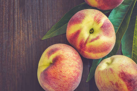 velvety: Peaches and leaves on dark wooden background. Top view with copy space Stock Photo