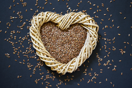 Flax seed in woven heart-shaped basket with flaxseed scattered around on dark background Stock Photo