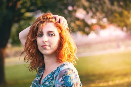 Girl with red hair and blue floral dress holding hand over her head and looking over shoulder. Plenty of copy space Stock Photo