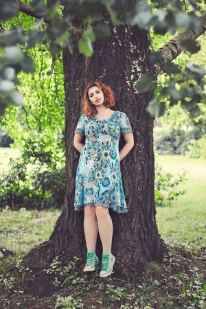 facing on camera: Girl with red curly hair and blue floral dress leaning against tree facing camera