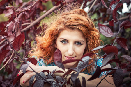 Girl with red hair and blue eyes looking at camera through black cherry plum leaves
