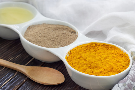 curcumin: Turmeric, black pepper and olive oil in white ceramic bowl on wooden background. Ingredients for golden paste