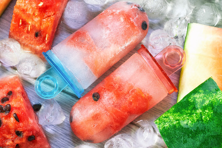 Frozen watermelon popsicles with ice cubes and watermelon slices on grey wooden background. Concept image for summer refreshments Stock Photo