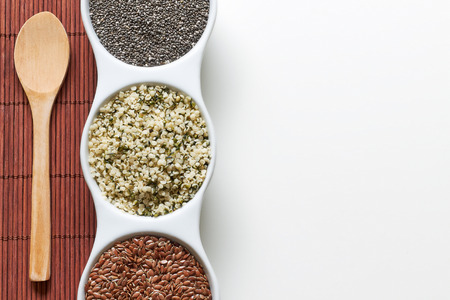 Chia, flax and hemp seeds in bowl on white background. Vegan sources of Omega-3. Top view with plenty of copy space 免版税图像
