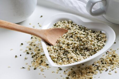 Hemp seeds in heart shaped ceramic bowl and wooden spoon on white background
