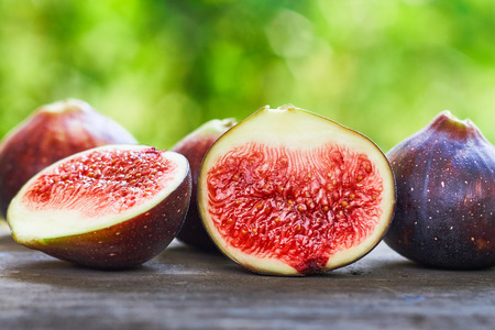 Fresh ripe black figs on rustic grey wooden table with green blurry background. Copy space