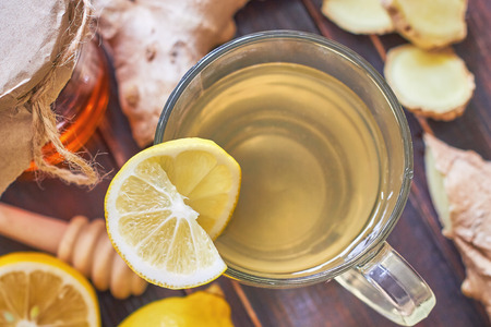 Ginger tea served with honey and lemon on wooden table. Top view