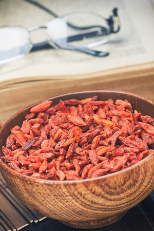 chinese wolfberry: Dried goji berries in wooden bowl as a healthy snack