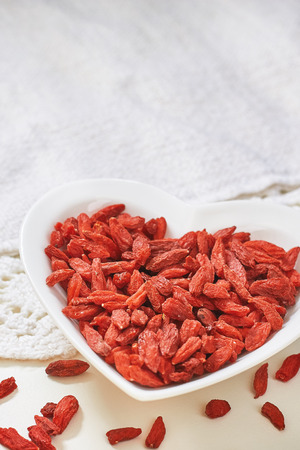 lycium: Dried goji berries in heart shaped ceramic bowl on white table. Copy space