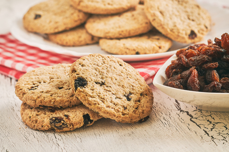 galletas integrales: Wholewheat biscuits with raisins on white rustic table Foto de archivo