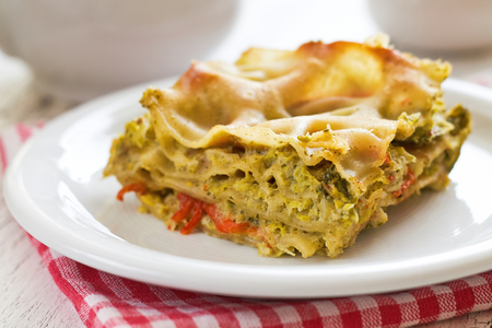 Vegan lasagna with savoy cabbage, tofu and red bell pepper served on white plate