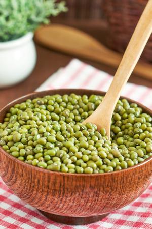 vigna: Raw mung beans (Vigna radiata) in wooden bowl Stock Photo