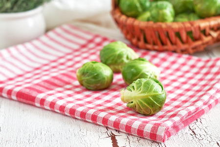 Fresh raw brussel sprouts on white rustic wooden background Stock Photo