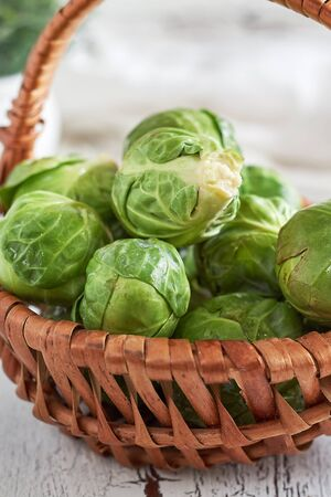 Fresh raw brussel sprouts in woven basket on white rustic wooden background Stock Photo