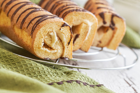 Sweet swiss rolls (roulade) with white cream on green tablecloth 免版税图像