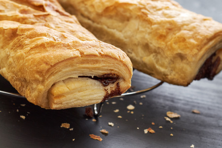 fil: Puff pastry with chocolate filling on black wooden background
