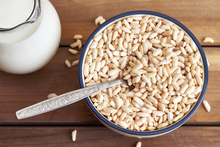 Puffed rice cereal in bowl with pitcher of milk on wooden background. Top view