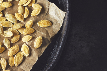 Roasted pumpkin seeds on black rustic background. Top view with copy space Stock Photo