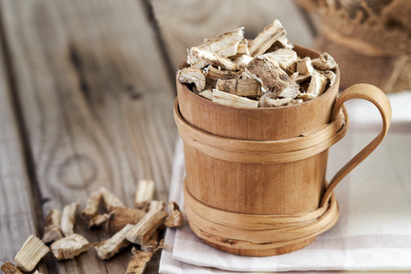 Marshmallow root (Althaea officinalis) in wooden cup. Copy space