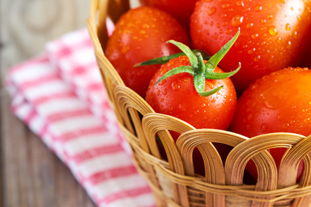 washed: Fresh cherry tomatoes in woven basket on wooden background. Copy space Foto de archivo