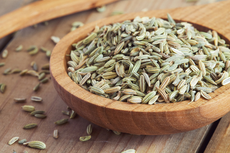 Pile of dried fennel seeds in wooden bowl