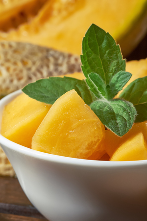 Sweet ripe cantaloupe melon cut and served with mint leaves