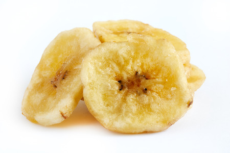 Homemade banana chips (dried and fried banana slices) isolated on white background