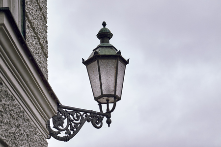 Old style street light attached to a wall. Moody weather. Copy space Stock Photo