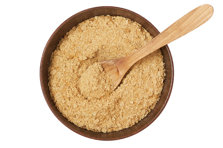 Nutritional brewers yeast flakes in wooden bowl isolated on white background. Top view Archivio Fotografico