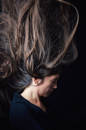 Girl throwing hair in the air on black background. Concept image for bad hair day Standard-Bild