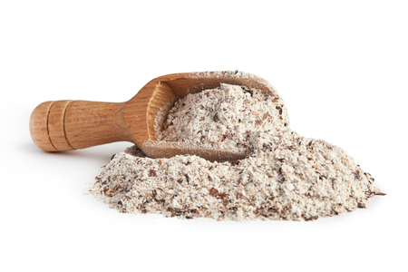 Pile of buckwheat flour with wooden scoop isolated on white background