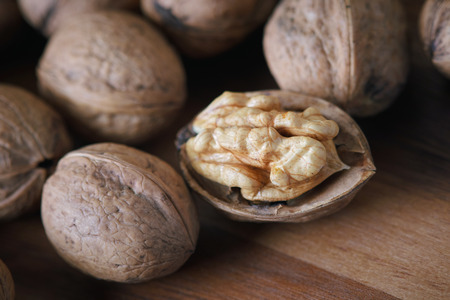Closeup of whole and kernel walnuts on wooden background