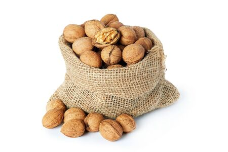 Whole walnuts (in shell) in burlap sack isolated on white background