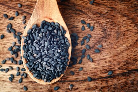 Black sesame seeds in wooden spoon. Top view with copy space